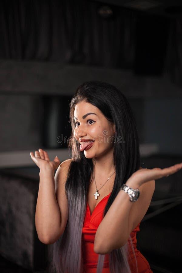Nätt ung kvinna som poserar för kamera och visar hennes tunga royaltyfria bilder