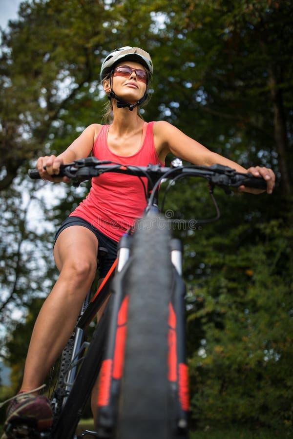 Nätt ung kvinna som rider hennes mountainbike fotografering för bildbyråer
