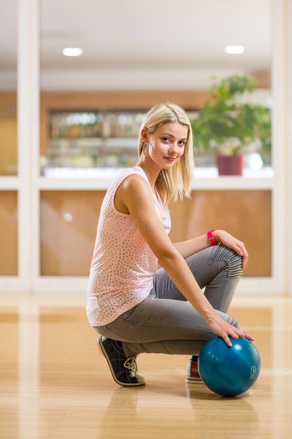 Nätt ung kvinna som rymmer en bowlingklot på bowlingklubban, arkivbild