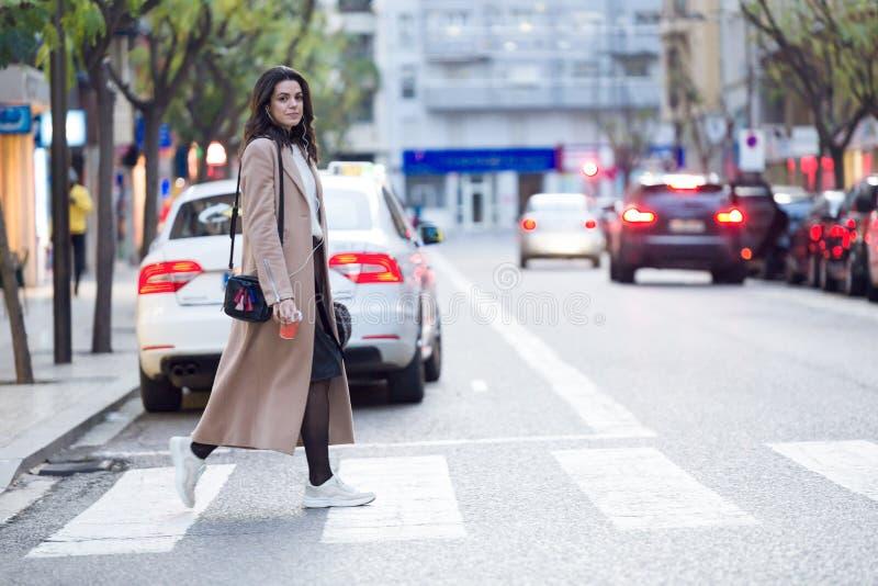 Nätt ung kvinna som rymmer kaffe och ser åt sidan, medan korsa gatan arkivfoto