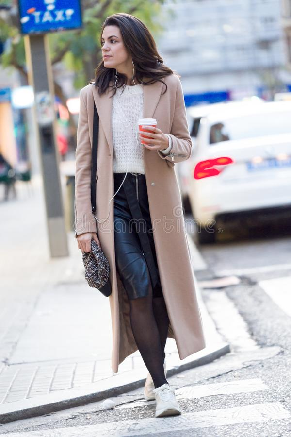 Nätt ung kvinna som rymmer kaffe och ser åt sidan, medan korsa gatan royaltyfri foto