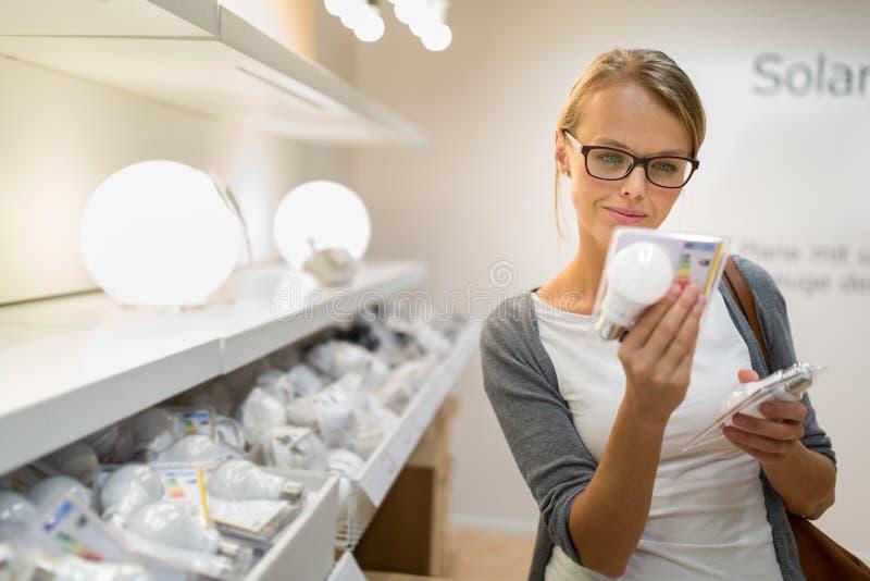 Nätt ung kvinna som rymmer och väljer en LEDD diod n royaltyfri foto