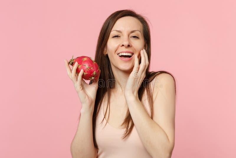 Nätt ung kvinna som sätter handen på kinden som rymmer den nya mogna pitahayaen, drakefrukt som isoleras på den rosa pastellfärga royaltyfri fotografi