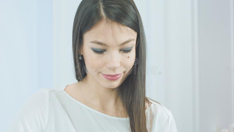 Nätt ung kvinna som sätter in vita hörlurar in i hennes öron för att lyssna till musiken arkivfoto