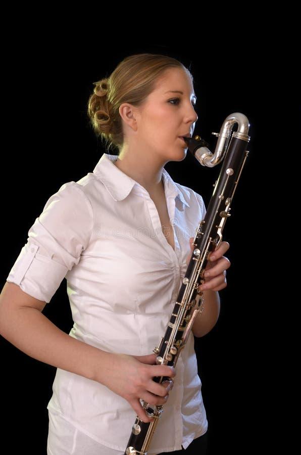 Nätt ung kvinna som spelar den bas- klarinetten royaltyfri foto