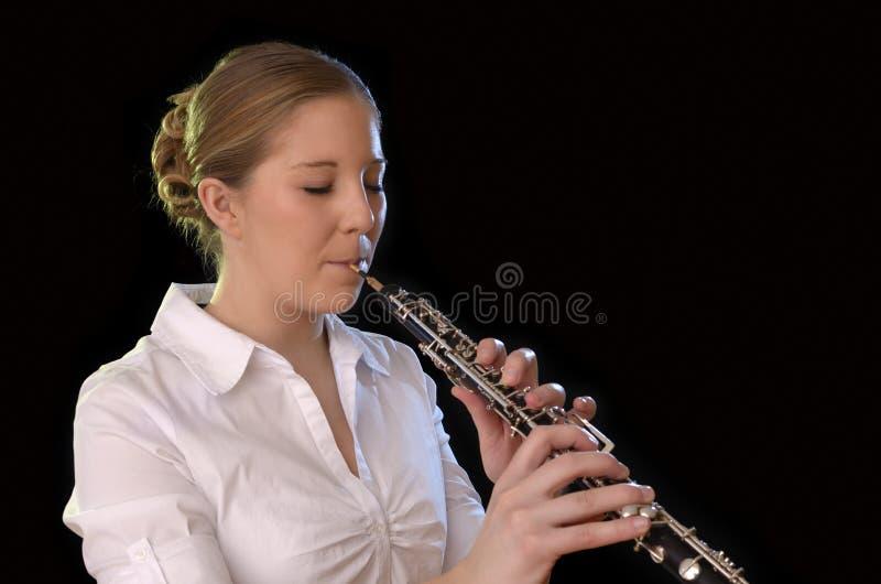 Nätt ung kvinna som spelar oboen arkivfoton