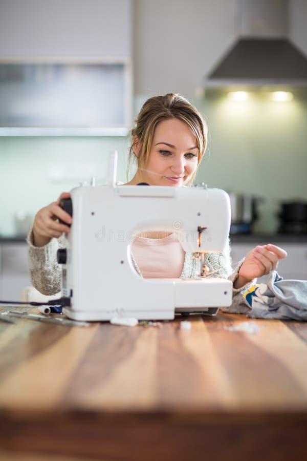 Nätt ung kvinna som syr kläder royaltyfria foton