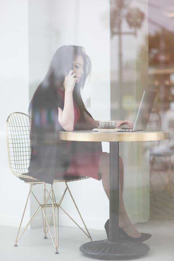 Nätt ung kvinna som talar av mobiltelefonen som sitter nära tabellen med bärbara datorn i kafé royaltyfri foto