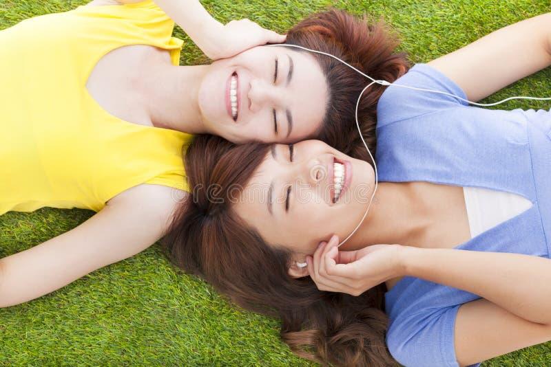 Nätt ung kvinna som två ligger på grässlätt och lyssnande musik royaltyfri bild