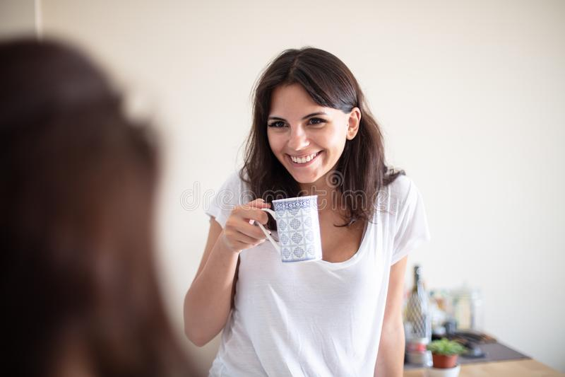 Nätt ung kvinna som tycker om kaffe med en vän arkivfoto