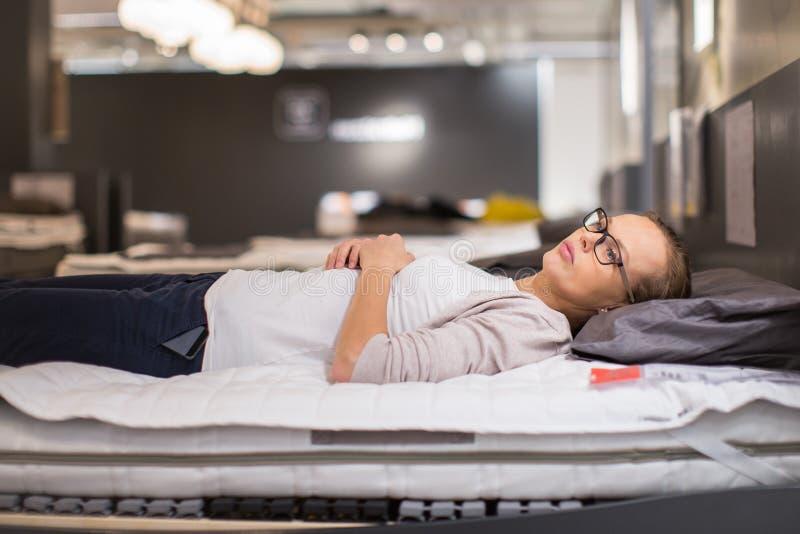 Nätt ung kvinna som väljer den högra sängen/mattrasen royaltyfri bild