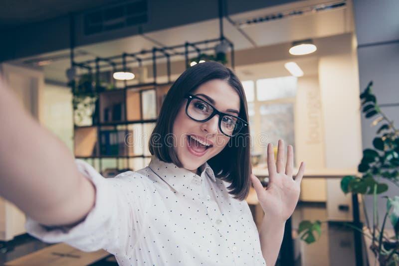 Nätt ung le flicka i exponeringsglas som tar en selfie som arbetar i ljus rumarbetsplatsarbetsstation som grimacing säga höga häl arkivbilder