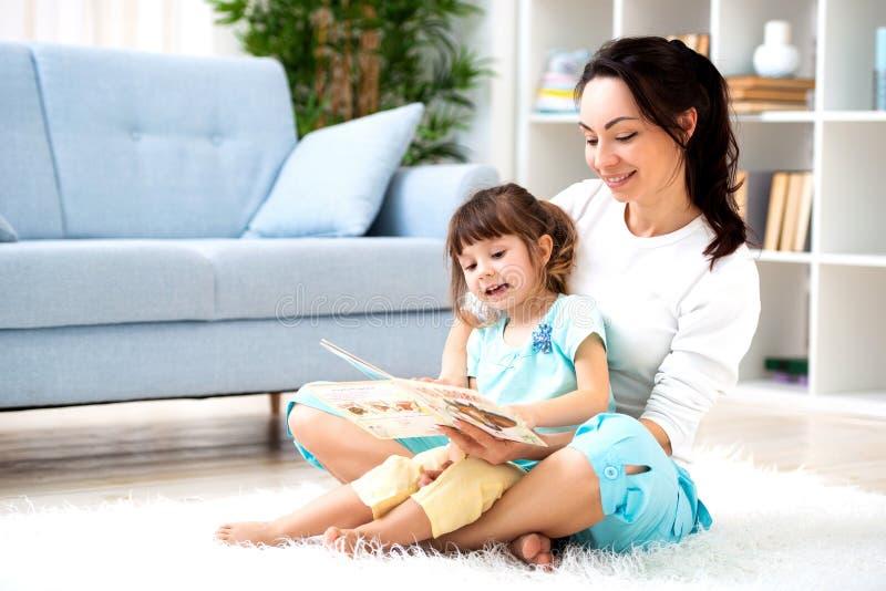 Nätt ung moder som läser en bok till hennes dotter som sitter på mattan på golvet i rummet Läsa med barn arkivbilder
