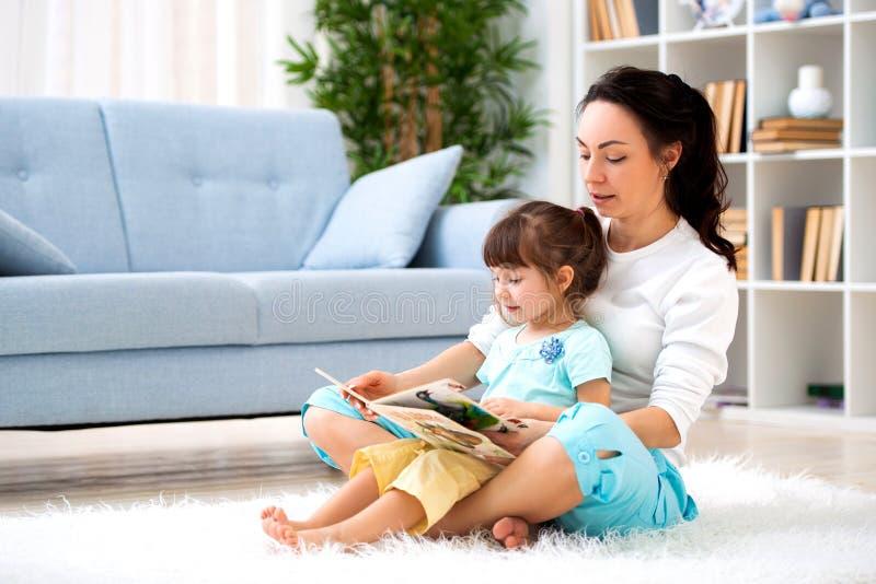 Nätt ung moder som läser en bok till hennes dotter som sitter på mattan på golvet i rummet Läsa med barn royaltyfri foto