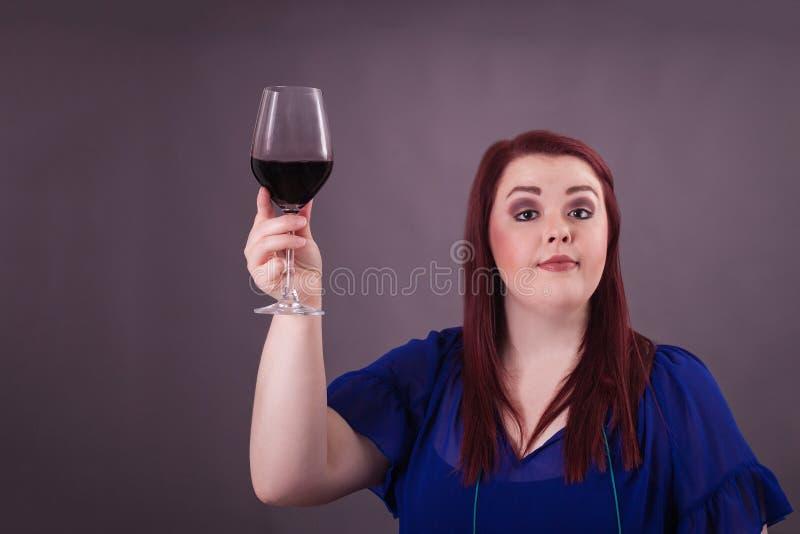 Nätt ung röd head dam som framlägger ett exponeringsglas av rött vin royaltyfri bild