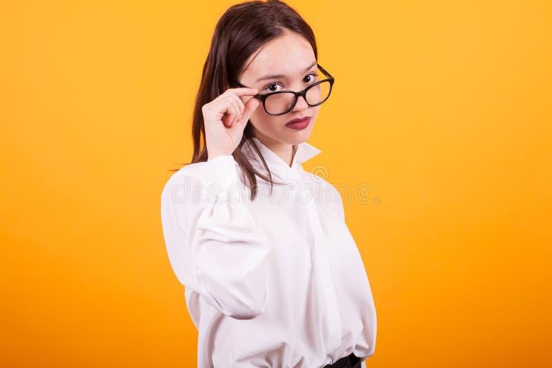 Nätt ung skolflicka som ser över glasögon i studio över gul bakgrund arkivbilder
