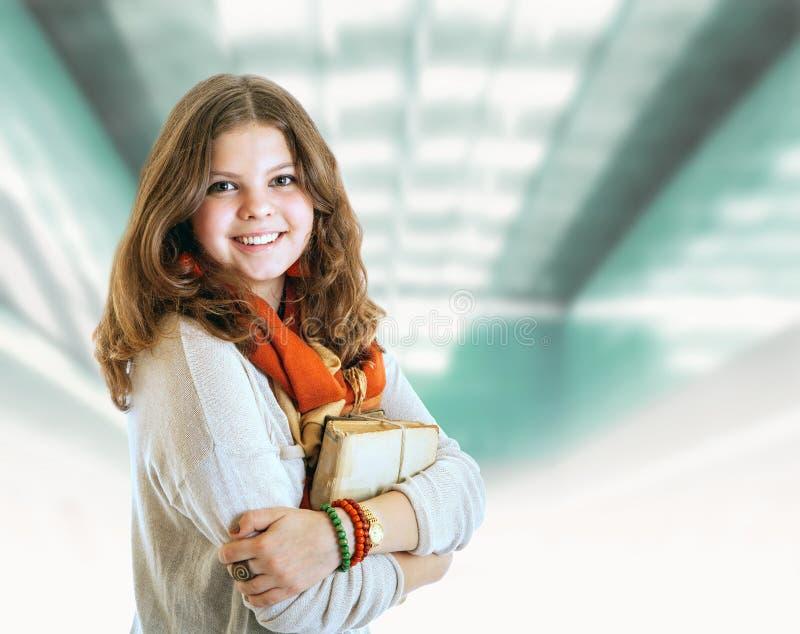 Nätt ung studentflickastående med böcker fotografering för bildbyråer