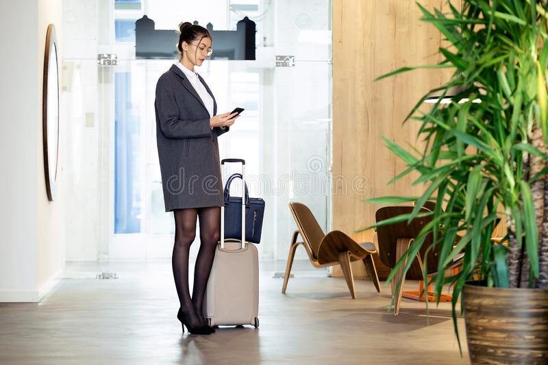Nätt ungt affärskvinnaanseende med resväskan, medan rymma hennes mobiltelefon på hotellkorridoren arkivbilder