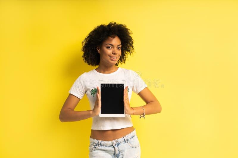 Nätt ungt afro amerikanskt kvinnaanseende och använda minnestavladatoren som isoleras över gul bakgrund arkivfoton