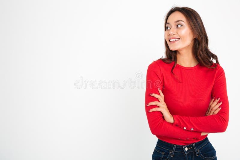 Nätt ungt lyckligt kvinnaanseende med korsade armar royaltyfri bild
