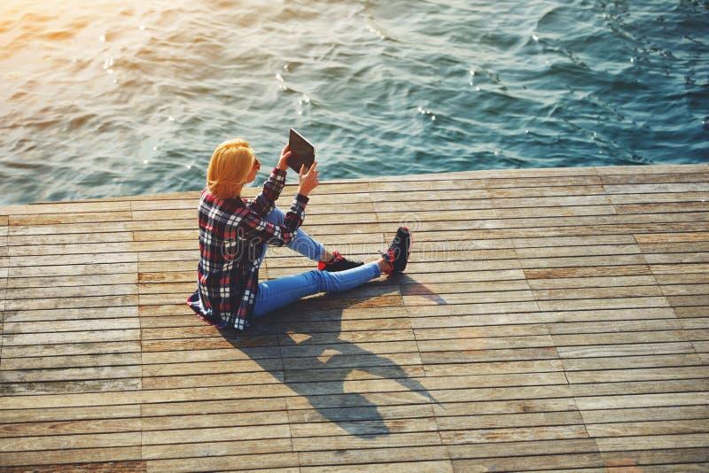 Nätt ungt sammanträde för kvinnlig student på en pir nära havet som tycker om det härliga vädret och fotograferar med hennes kame arkivbild