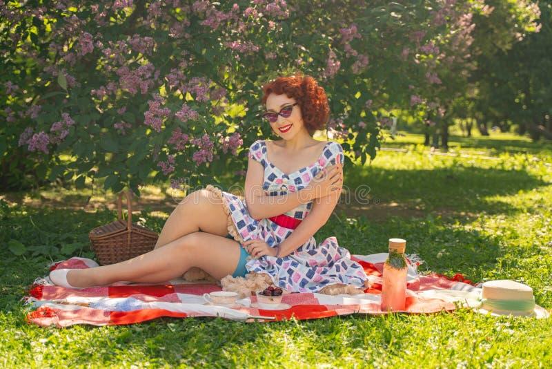 Nätt ungt stift upp flickan som har att vila på naturen lycklig slank bärande tappningklänning för ung kvinna som sitter på tarta royaltyfri bild