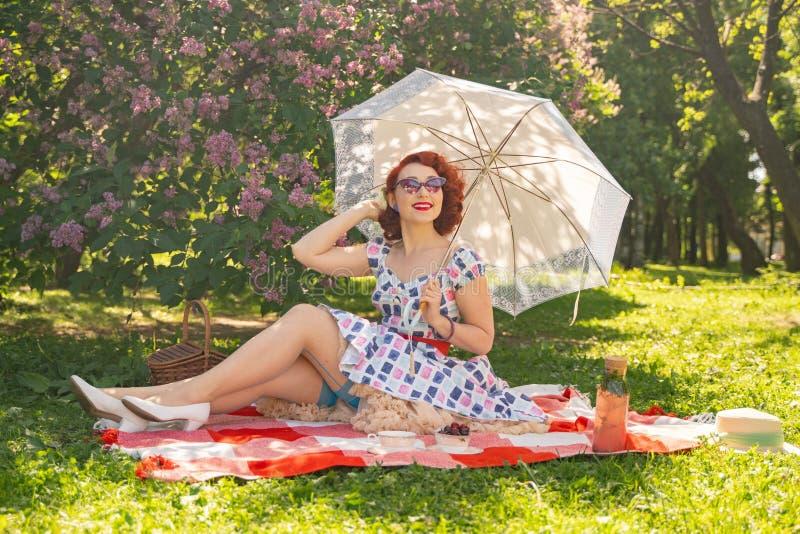 Nätt ungt stift upp flickan som har att vila på naturen lycklig slank bärande tappningklänning för ung kvinna som sitter på tarta royaltyfria foton