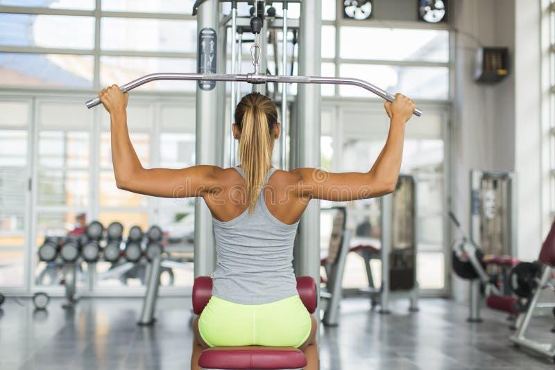 Nätt utbildning för ung kvinna i idrottshallen royaltyfria foton