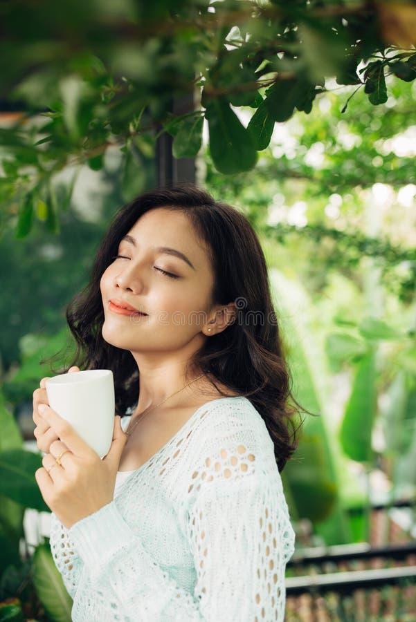 Nätt vietnamesisk kvinna som tycker om hennes morgonkaffe på en veranda arkivbild