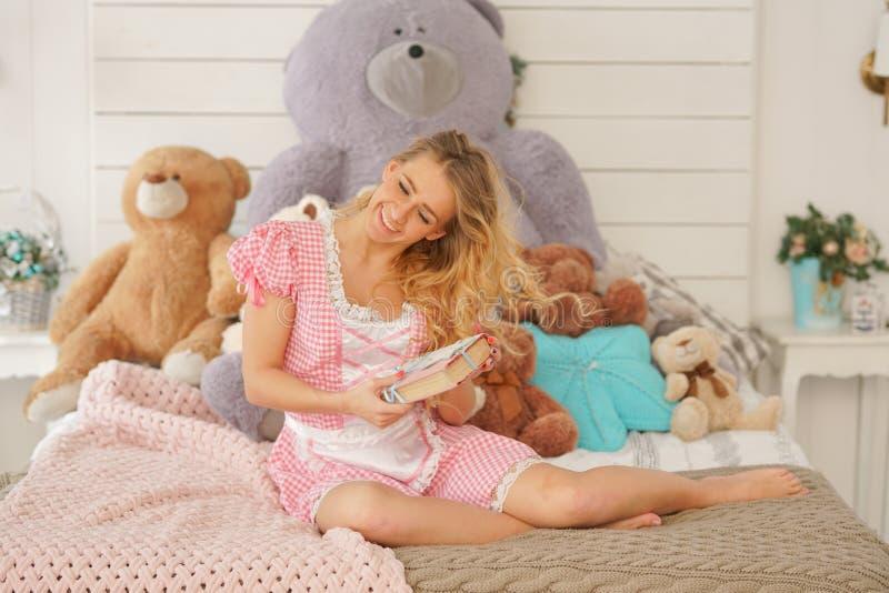 Nätt vuxen flicka med hennes hemliga dagbok i hennes vita sovrum med många flotta nallebjörnar arkivfoton