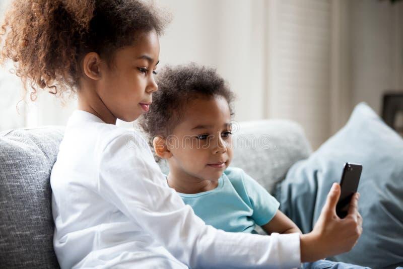 Nätta afrikansk amerikanbarn använder smartphonen royaltyfria bilder