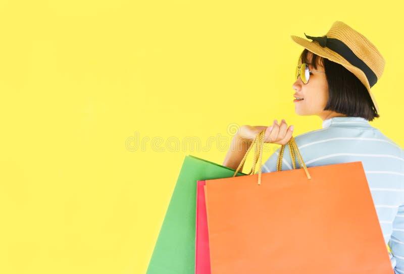 Nätta barnflickahänder som rymmer den shoppa påsen, isolerade på gul bakgrund - asiatisk lycklig sommar för den unga kvinnan som  royaltyfria foton