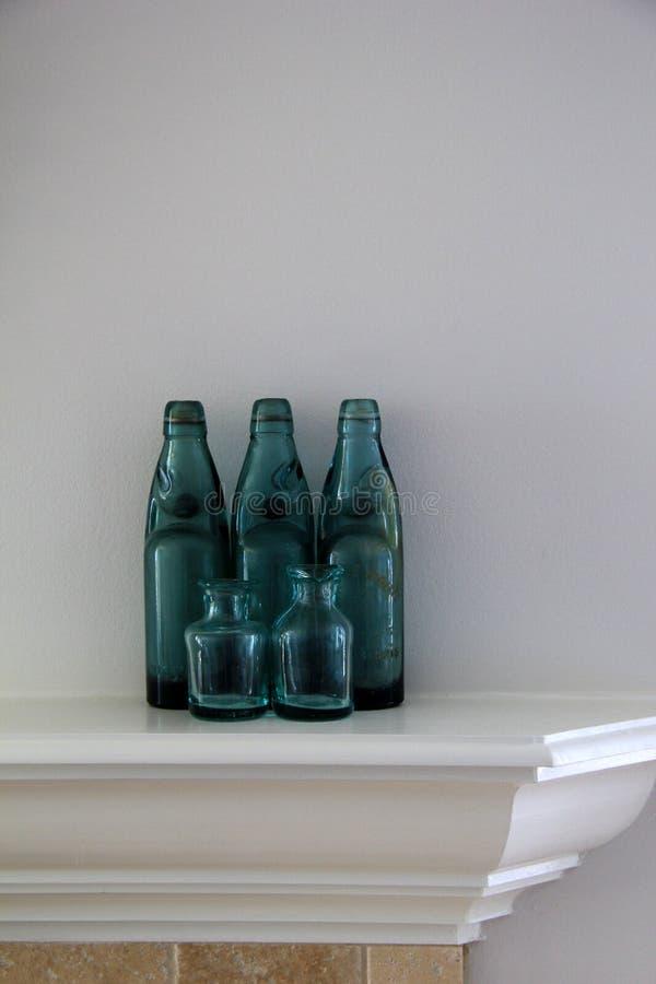 Nätta blåa flaskor på det vita ansvaret av hemmet fotografering för bildbyråer