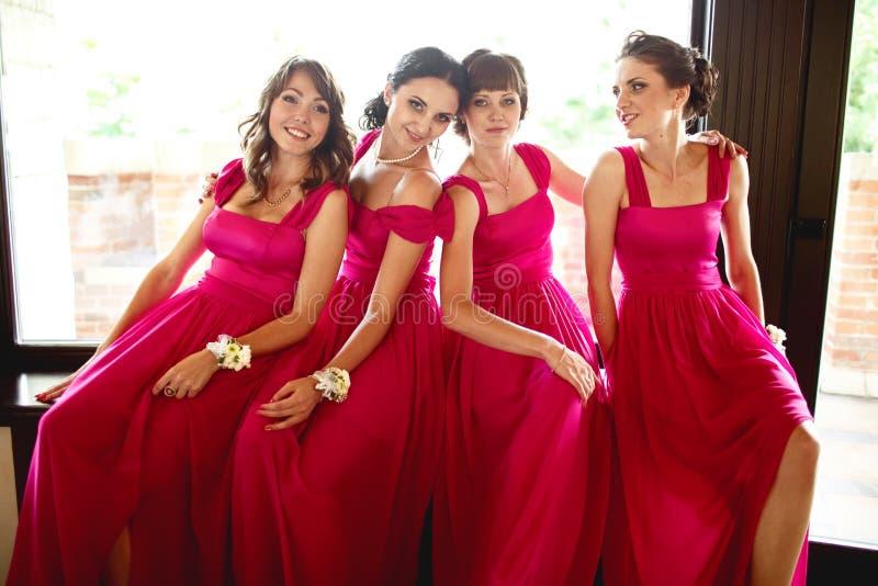 Nätta brudtärnor i rosa klänningar sitter bak ett stort fönster royaltyfria foton