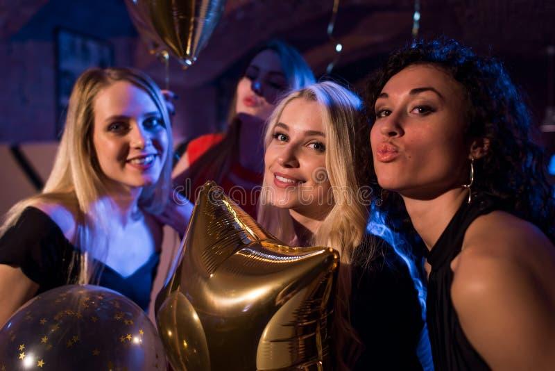 Nätta europeiska flickor som ler och att blåsa kyssar som har partiet på nattklubben arkivfoto