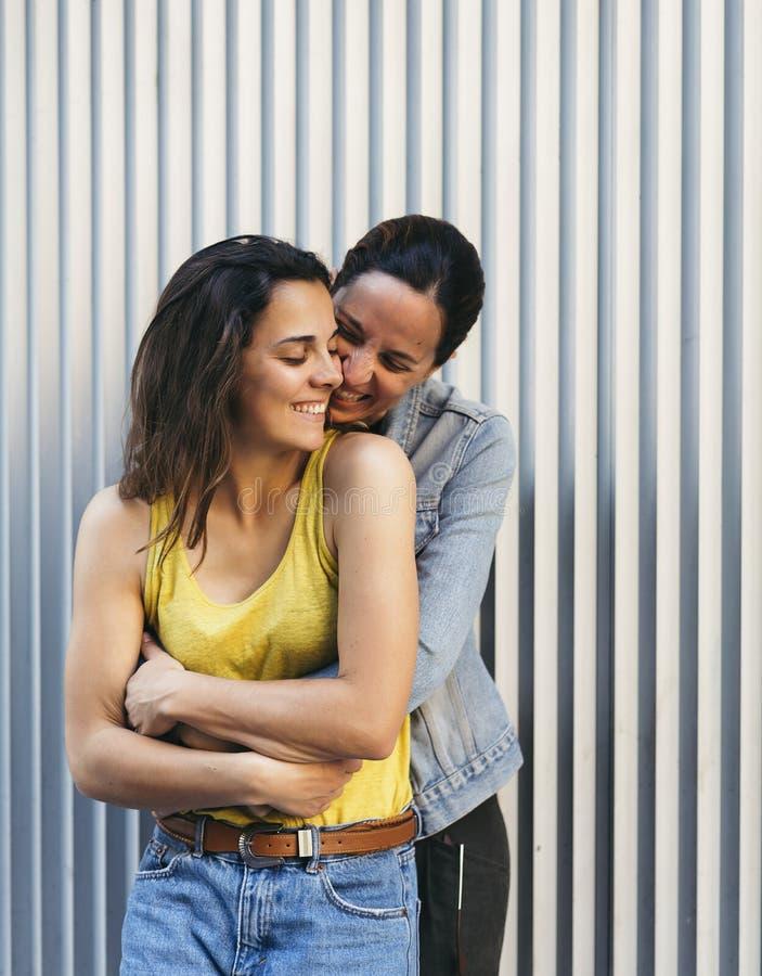 Nätta flickapar som kramar sig och att le, affektion, förälskelse och samma, könsbestämmer förhållandebegrepp arkivfoton