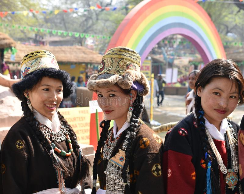 Nätta flickor, i traditionella indiska stam- klänningar och att tycka om mässan