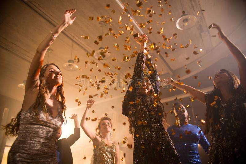 Nätta flickor som dansar i konfettidusch arkivfoto