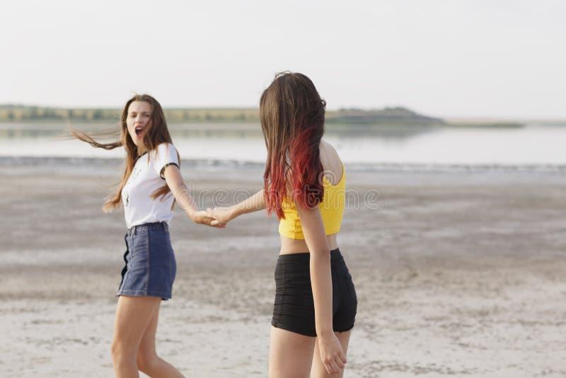 Nätta flickor som har gyckel på en naturlig bakgrund Tonåringar som kör nära sjön Kvinnligt kamratskapbegrepp kopiera avstånd royaltyfri bild