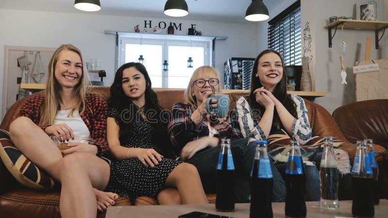 Nätta flickvänner håller ögonen på och diskuterar film på TV Lyckliga le kvinnliga vänner tycker om ultrarapid 4K för komedifilme royaltyfria bilder