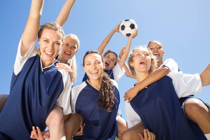 Nätta fotbollsspelare som firar deras seger royaltyfri foto