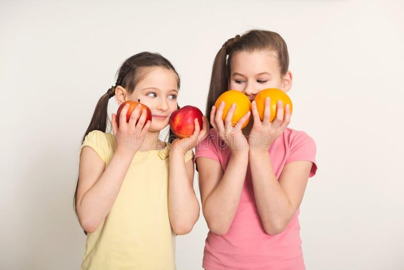 Nätta gulliga små flickor med frukter över vit bakgrund royaltyfri bild