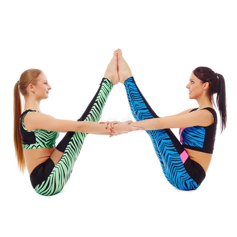 Nätta gymnaster som poserar i par som isoleras på vit arkivfoton
