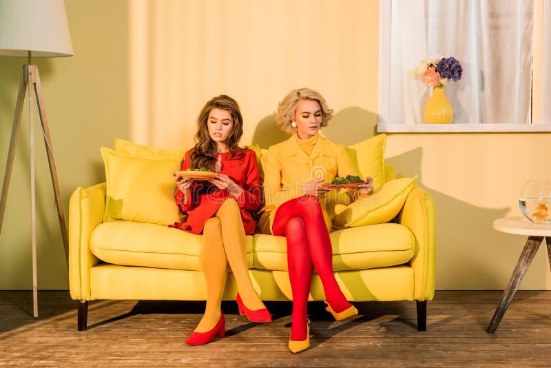 nätta kvinnor i retro kläder med grönsaker på plattor som sitter på den gula soffan på den ljusa rumdockan arkivbild
