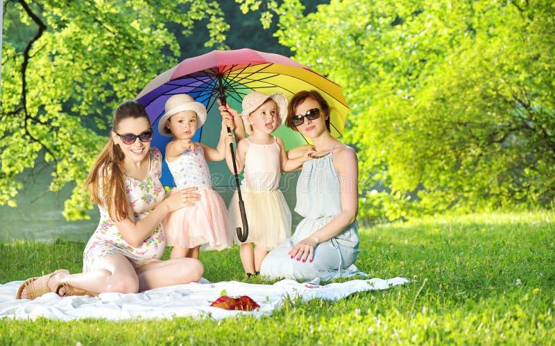 Nätta kvinnor och små flickor som vilar på filten royaltyfri bild