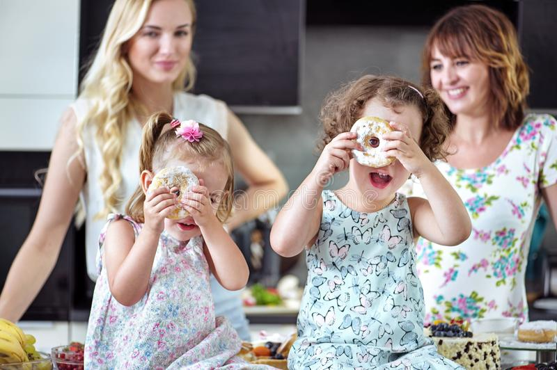 Nätta kvinnor som äter sötsaker med deras barn arkivfoton