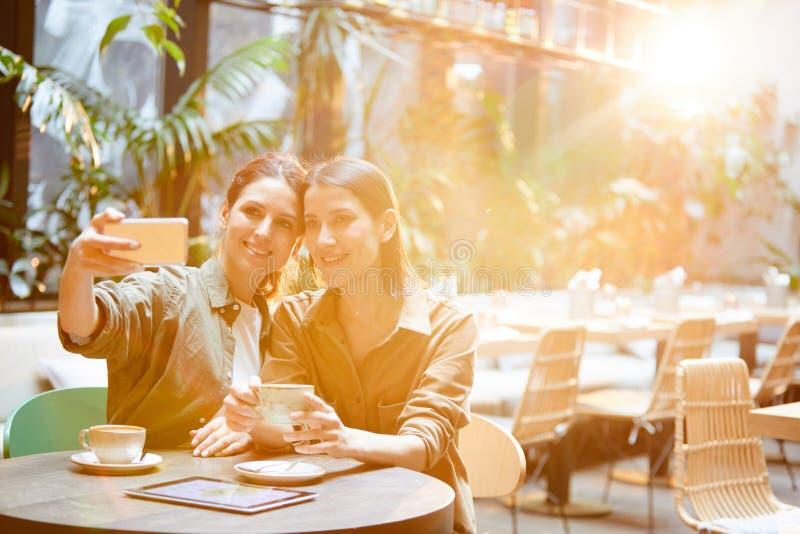 Nätta kvinnor som talar selfie i tropiskt kafé arkivbilder