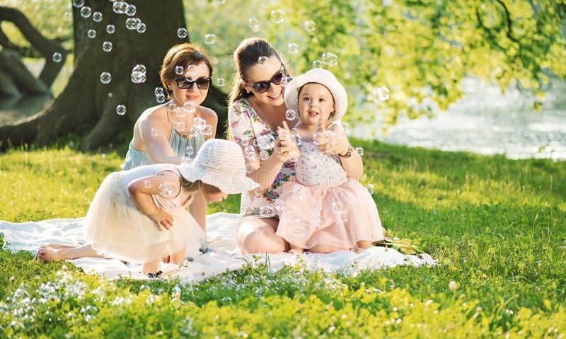 Nätta kvinnor som vilar på filten med små döttrar fotografering för bildbyråer