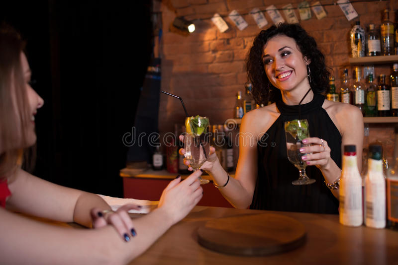 Nätta le erbjudande drinkar för kvinnlig bartender till gäster som står bak stångräknare royaltyfri fotografi