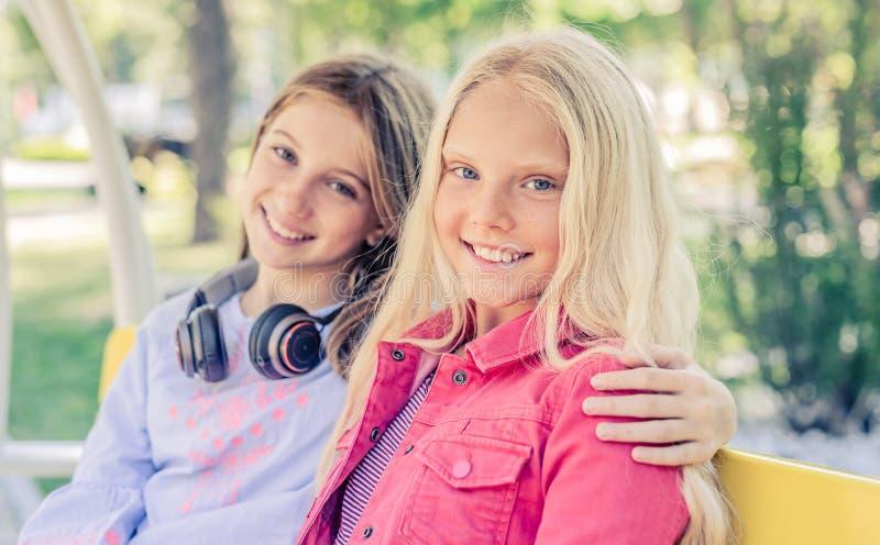 Nätta le tonårs- flickor sitter att krama tillsammans royaltyfria foton